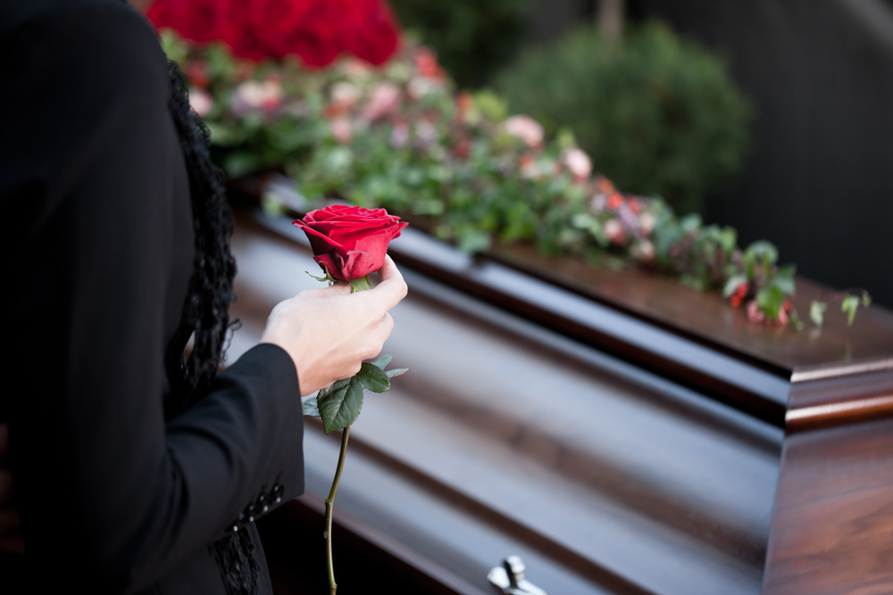 Mourner holding rose next to coffin