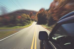 Car speeding on a winding scenic drive