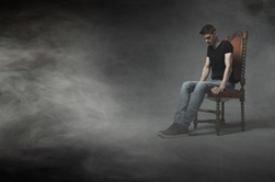 Man Sitting in a Chair Surrounded by Fog