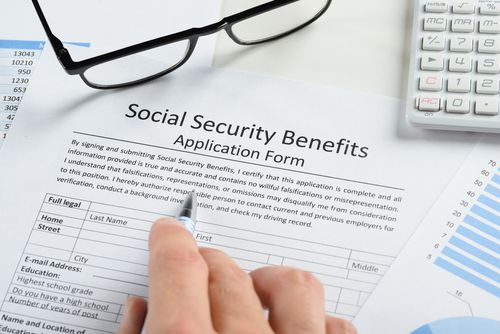 A Hand Over a Social Security Benefits Form With Glasses and a Calculator