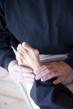 A doctor inspecting a bunion on someone's foot