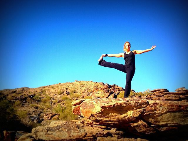 Woman doing Yoga on a rock