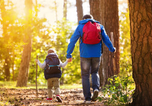 father hiking in forest with son, wearing backpacks