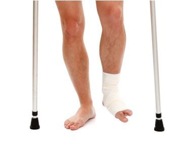 Legs of someone with an injured ankle with crutches