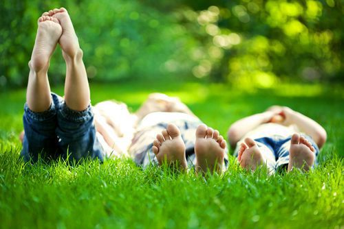 Children laying in grass with bare feet