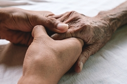 A Hand Holding an Elderly Patient's Hand While in a Nursing Home