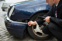 Car Reconstructionist Examining a Car After a Collision