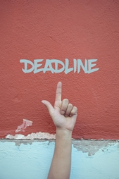 Hand Pointing to Deadline on a Red Wall