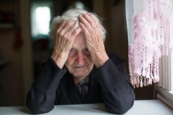 Distraught Elderly Woman With Head on Hands