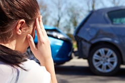 A Distraught Woman Looking at a Car Wreck