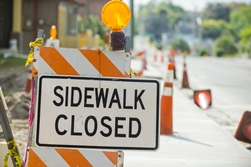 Sidewalk Closed Sign by a Busy Construction Zone