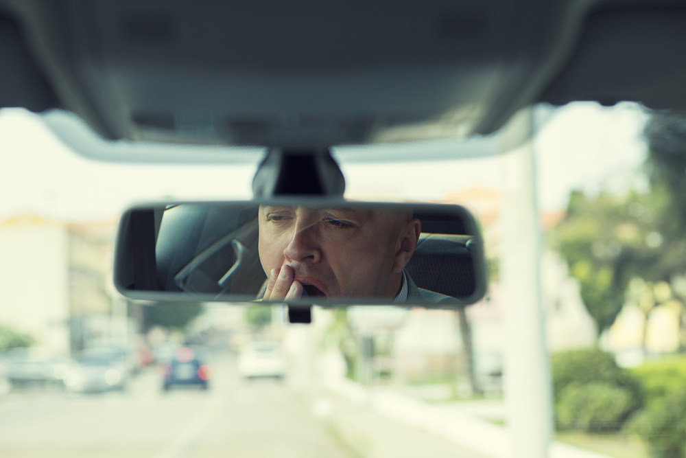 drowsy driver in rear view mirror