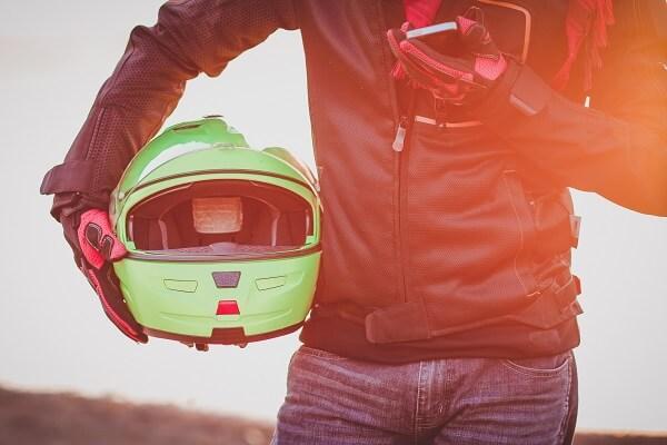 motorcycle rider holding helmet