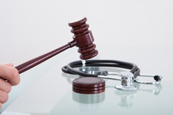 Hand Holding a Gavel With a Stethoscope in the Background