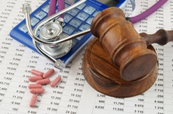A Wooden Gavel, Calculator, Stethoscope, and Medication Sitting on a Medical Bill