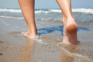 Healthy feet walking in water on the beach