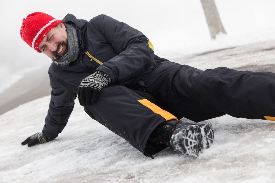 Man holding hurt leg after falling on ice