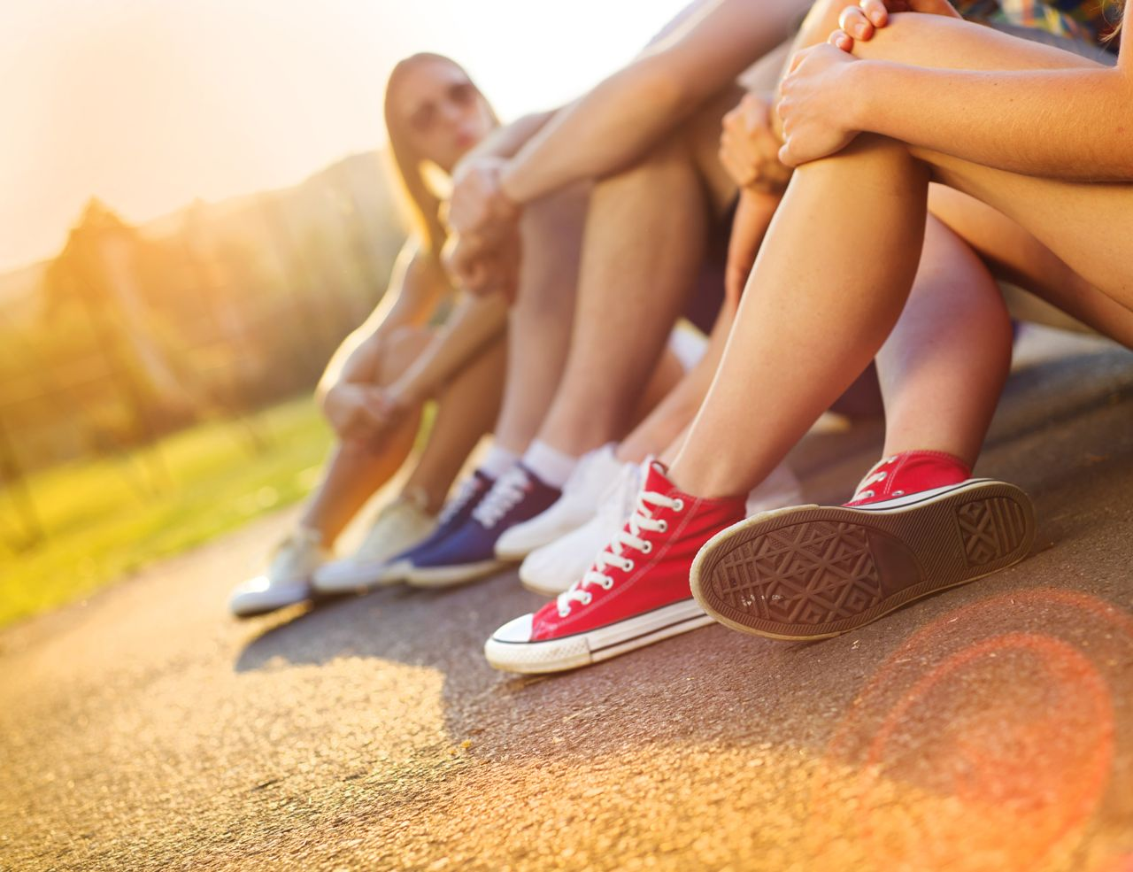 Teenagers sitting on pavement