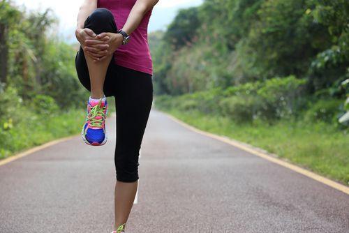 Woman dynamically stretching her leg