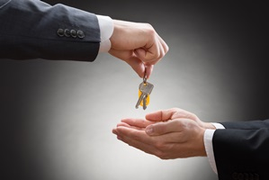Business man handing two keys to colleague