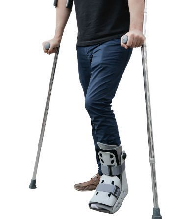 person walking with immobilization boot and crutches