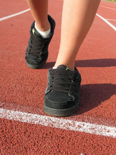 Runner on Track with Black Skateboard Shoes