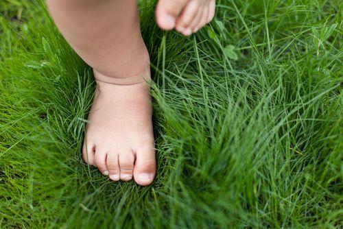 feet of child running through grass