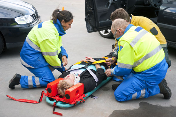 Paramedics treating patient with spinal damage
