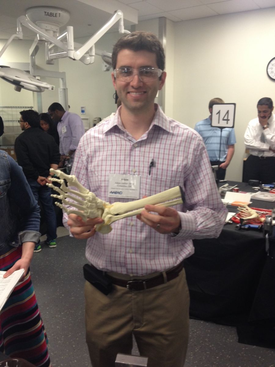 Dr. Adam Gerber hold a model foot bone.
