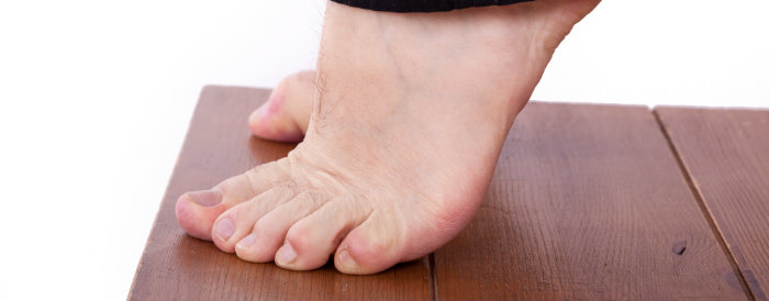 feet standing on tiptoe on a wooden surface