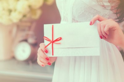 girl holding gift envelope wrapped in red ribbon