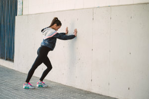 woman in workout gear stretching against a wall