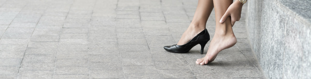 woman holding back of heel, wearing black high heel shoes