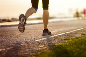 closeup of shoes of woman running down paved trail