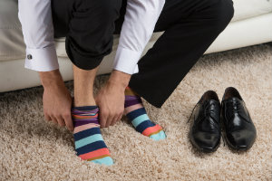 Man pulling up striped socks with dress shoes beside him