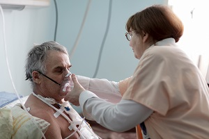 Nurse adjusting oxygen mask on older patient