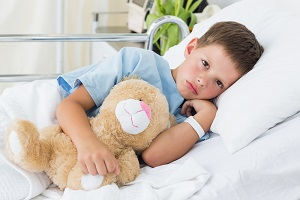 Little boy with teddy bear waits in hospital bed