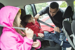 Dad buckles the kids into their safety seats in the car