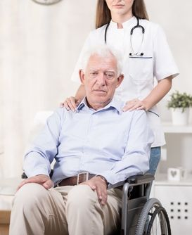 Elderly man in wheelchair being pushed by a female healthcare worker