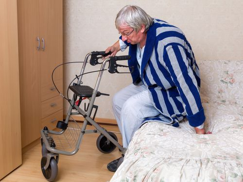 Elderly man leaning on rolling walker to get out of bed