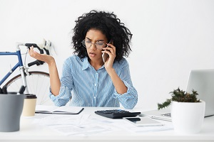 A professional woman is upset by a phone call about her insurance coverage denial