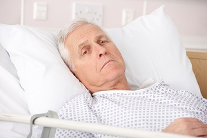 Older man is uncomfortable in a hospital bed