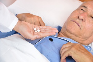 Doctor gives medication to elderly man in bed