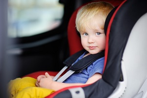A toddler is secured in his forward-facing car seat