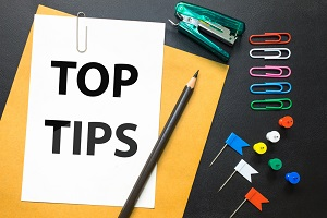 Amid a scattering of office supplies is a sign reading TOP TIPS
