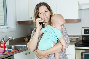 Woman on the phone while holding her baby in her arms