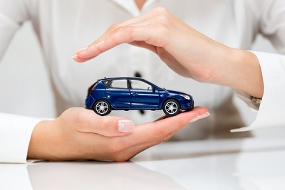 Small car held in hands resembling car insurance protection