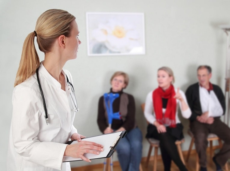 Female doctor holding clipboard in doctors office