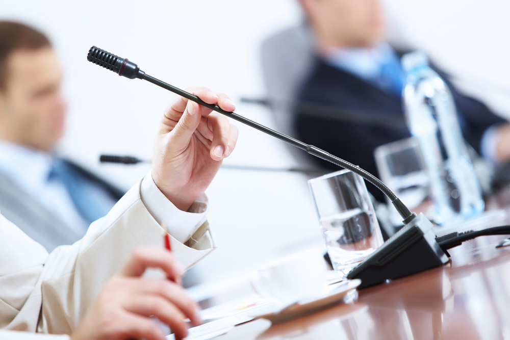 close-up of man holding microphone at conference table