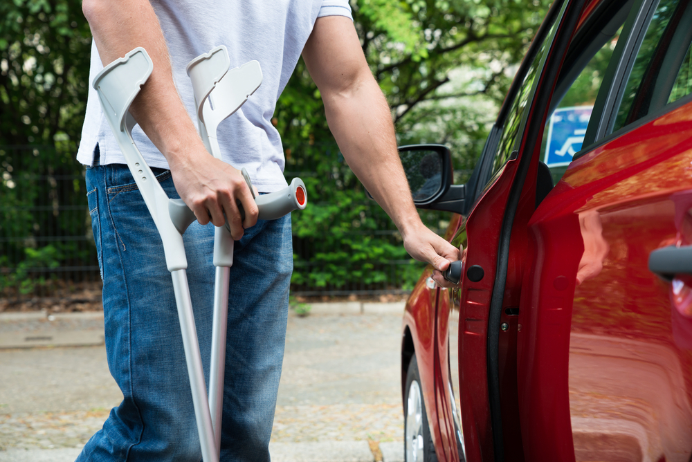 Man with crutch opening a car door
